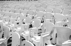 Reihen von weißen Stühlen am Konzert Stockbild
