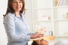 Reiki healing. Professional Reiki healer doing reiki treatment to young woman royalty free stock photos