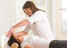 Reiki healing. Professional Reiki healer doing reiki treatment to young woman stock photo