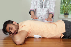 Reiki healing session. Reiki session by experienced healer with focus on therapists hands positioned over back of men stock photos