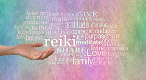 Reiki Healing Words of Love. Female hand outstretched with the word 'reiki' leaving her hand, surrounded by a relevant healing word cloud on a wide rainbow stock photography
