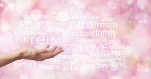 Reiki in the palm of your hand. Female hand outstretched with the word REIKI floating above, surrounded by healing related words on a wide pink colored bokeh Stock Photography