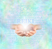 Reiki Share. Female hands cupped with the word 'Reiki' floating above, surrounded by a relevant healing word cloud on a misty sparkling ethereal blue energy Royalty Free Stock Photography