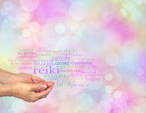 Reiki Share word cloud. Female hands cupped with the word 'Reiki' floating above, surrounded by a relevant healing word cloud on a pastel colored bokeh royalty free stock photography