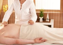 Reiki treatment. Hands over patient't back during reiki treatment Stock Image