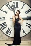 Reina de Elecant en el vestido negro que presenta cerca del reloj Foto de archivo