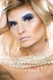 Reina joven de la nieve de la belleza en flashes de hadas con la corona del pelo en su cierre de la cabeza para arriba en luz azu Fotografía de archivo