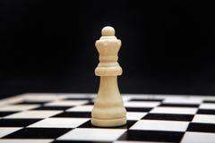 Reina y tablero de ajedrez blancos en un fondo negro Foto de archivo