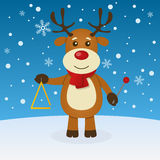 Reindeer Christmas on the Snow. Happy cartoon reindeer character playing the triangle in a snowy scene. Eps file available Stock Photo