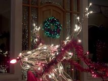 Reindeer at the Door. Wire and lights Christmas decorative reindeer in front of wreath-decorated door Stock Photography