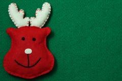 Reindeer on felt background. Red reindeer on green felt background Stock Images