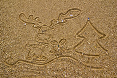 Reindeer, gift and christmas tree drawn on sand