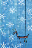 Reindeer made from dry sticks on wooden, blue background. Snow flaks image, ornament, craft Royalty Free Stock Image