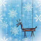 Reindeer made from dry sticks on wooden, blue background. Snow flaks image, ornament, craft Stock Photo