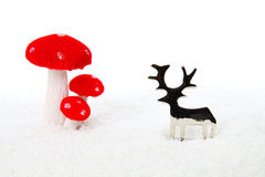Reindeer and mushroom Christmas decoration. In snow on white background Royalty Free Stock Photo