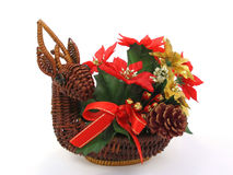 Reindeer ornament on white background. Christmas ornament. Reindeer shaped basket filled with red and golden flowers, leaves, a pine cone and a red bow Stock Photos