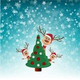 Reindeer peek from behind Christmas tree Royalty Free Stock Image