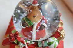 Reindeer with presents. A beautifull christmas globe with a raindeer holding some presents Royalty Free Stock Photo