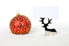 Reindeer with red bauble and business card. Reindeer holding business card with red bauble in snow on white background Royalty Free Stock Images