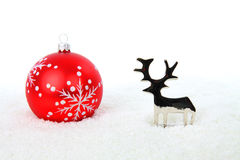 Reindeer and red christmas ball in snow. Reindeer and christmas bauble in snow on white background Stock Photos