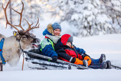 Reindeer safari. Family of mother and little girl at reindeer safari in winter forest in Lapland Finland Stock Image