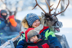Reindeer safari. Family of mother and little girl at reindeer safari in winter forest in Lapland Finland Stock Photo