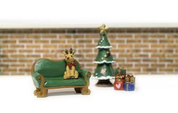 Reindeer sitting on long green bench near Christmas tree Royalty Free Stock Photo