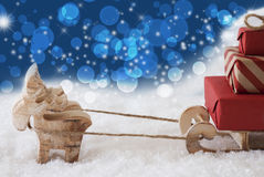 Reindeer With Sled, Blue Bokeh And Stars Background, Copy Space Stock Photo