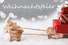 Reindeer With Sled, Silver Background, Weihnachtsfeier Means Christmas Party. German Text Weihnachtsfeier Means Christmas Party. Moose Is Drawing A Sled With Red stock photos