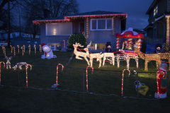 Reindeer and sleigh in candy cane fenced lawn Stock Photo
