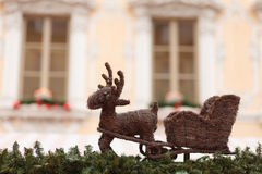 Reindeer with sleigh on the roof of a christmas market stand. The reindeer with the sleigh is usually transporting Santa Claus. Here it is used as decoration on Stock Photography