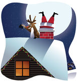 Reindeer takes a selfie with Santa stuck in the chimney Royalty Free Stock Photo