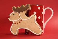 Reindeer vanilla cookie biscuit with red polka dot cup of coffee close up stock image