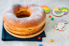 Reindling - Austrian or German festive yeasty baking for Easter. Ring brioche cake served on a wooden plate on a white stone background Stock Photography