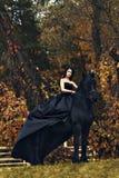 Reine noire de sorcière à cheval sur un cheval noir dans une forêt foncée sinistre sombre comme dans un conte de fées effrayant d image libre de droits