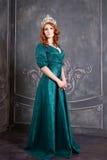 Reine, personne royale avec la couronne, cheveux rouges et robe verte Images stock