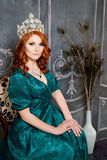 Reine, personne royale avec la couronne, cheveux rouges et robe verte Photographie stock