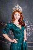 Reine, personne royale avec la couronne, cheveux rouges et robe verte Image libre de droits