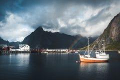 Reine, September 2018: Schip met binnen regenboog op de achtergrond in de haven van beroemde toeristische attractie van Reine royalty-vrije stock foto's