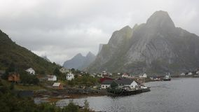 Reine. Traditional fishing village with rorbu - wooden cabins and characteristic rock behind it, Lofoten peninsula, Norway Royalty Free Stock Images