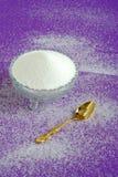 Reiner weißer granulierter Zucker auf einem purpurroten Hintergrund Lizenzfreie Stockfotografie