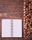 Reines Notizbuch für Menü, Rezeptaufzeichnung auf Draufsicht des Holztischs Kaffeebohnen als Hintergrund Lizenzfreies Stockbild