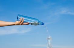 Reines Wasser goss overhand von einer Flasche in ein Glas Stockfoto