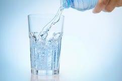 Reines Wasser wird in ein Glas Wasser von der Flasche geleert lizenzfreie stockfotografie