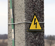 Reinforced concrete electricity pole with sign warning caution electricity shock risk high voltage keep out hazard Royalty Free Stock Images