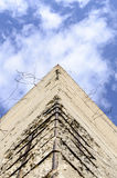 Reinforced concrete. Fragment of old obsolete reinforced concrete structures with rusty iron rods outside. The pyramid of concrete looks at the blue sky Stock Image