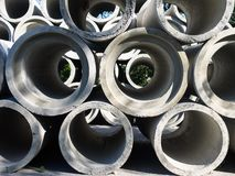Reinforced concrete pipes are stacked in several rows, prepared for loading. royalty free stock photos