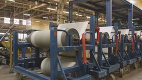 Reinforcement Textile in Rolls on Trolleys at Plant. Reinforcement textile in rolls on industrial metal trolleys moving along powerful tire production plant stock video footage