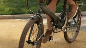Reinigen von Fahrradfelgen Schließen Sie herauf Fahrradreiten der jungen Frau am Straßenpark stock video footage