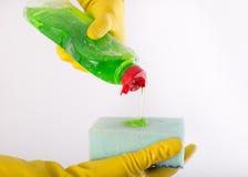 Reinigendes Gießen des Abwasches auf Schwamm Stockbilder